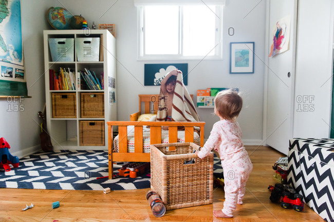 A baby watches her brother play