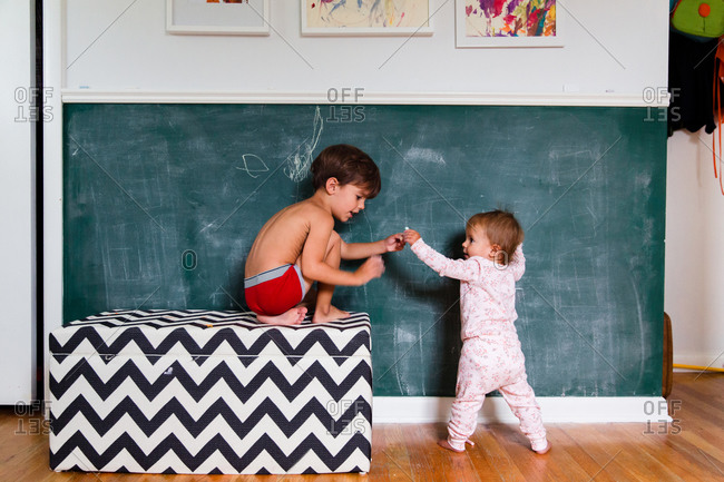 A baby hands her brother some chalk