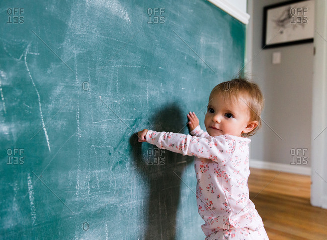 A baby draws on a chalk wall