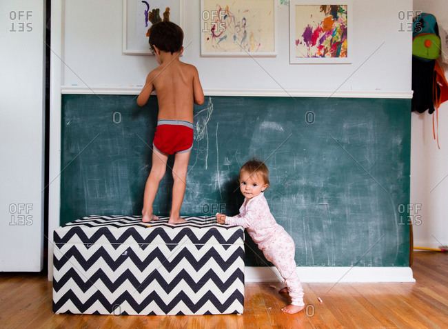A baby and her brother use a chalk wall