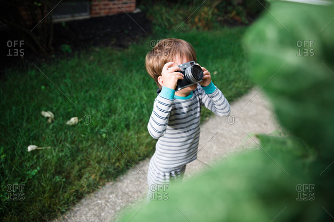 A boy uses a camera outdoors