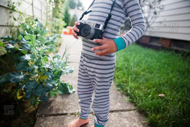A boy wears a camera outside