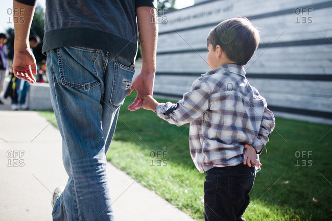 A boy holds his father's hand