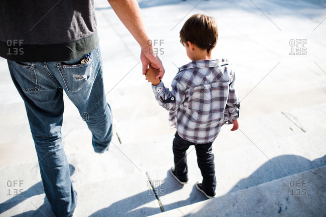 A boy walks down stairs with his father