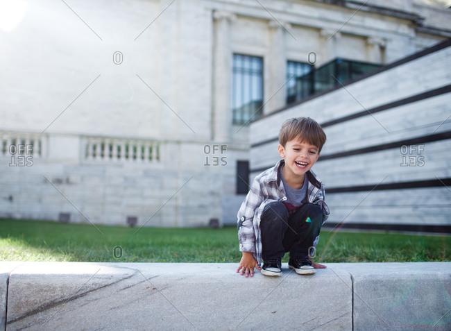 A boy squats on a wall