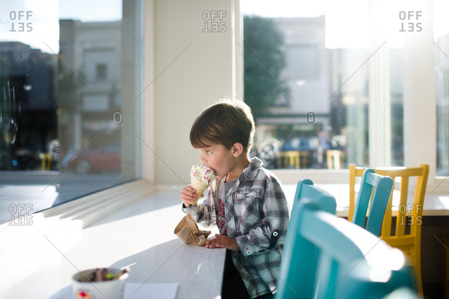 A boy takes a bite of his ice cream