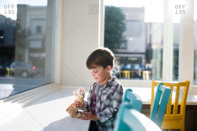 A boy looks at his ice cream cone
