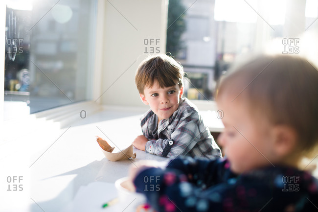 A boy looks at his baby sister at an ice cream shop