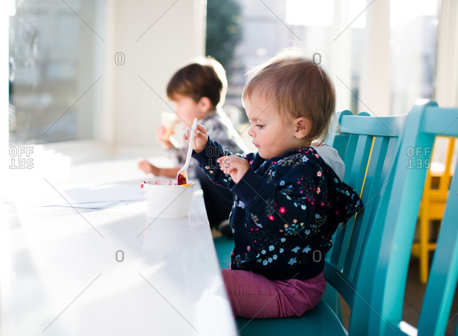 Two children sit at a counter in an ice cream shop