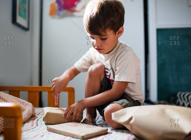 A young boy colors some packages