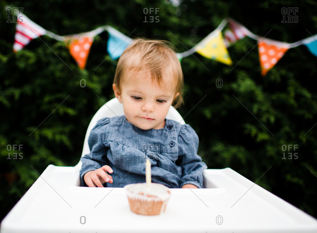 A baby looks at her cupcake