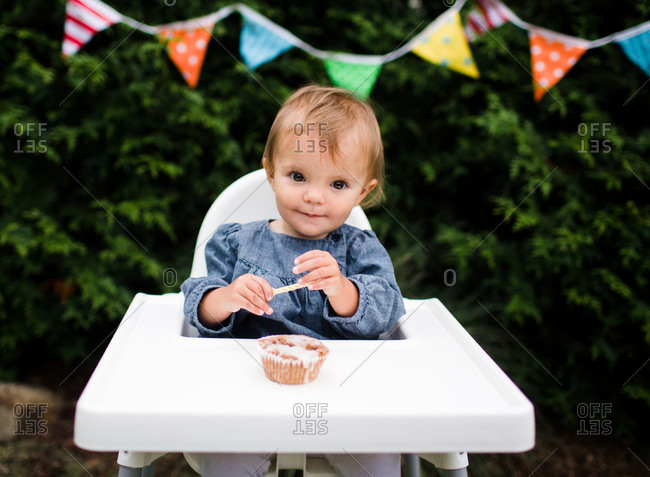 A baby holds a candle from her birthday cupcake