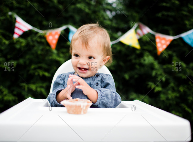 A baby smiles in front of a cupcake