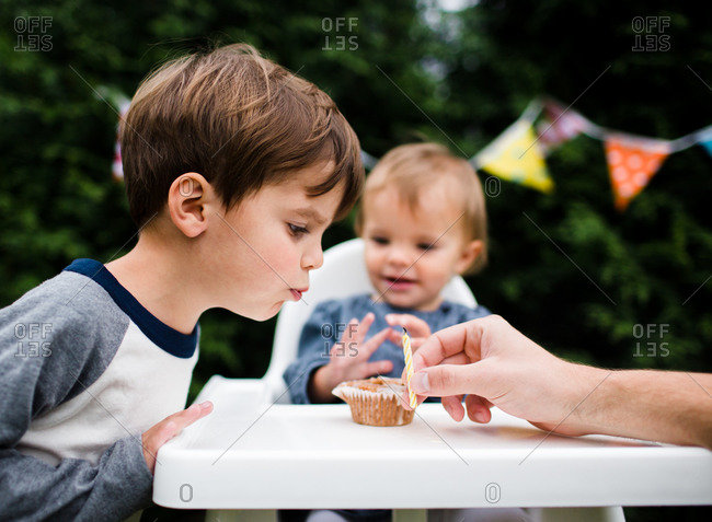 A young boy helps his baby sister blow out her birthday candle