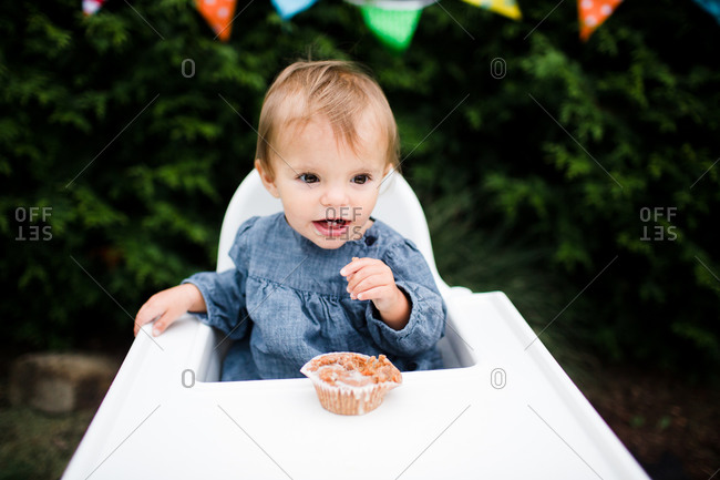A baby sits in front of a cupcake