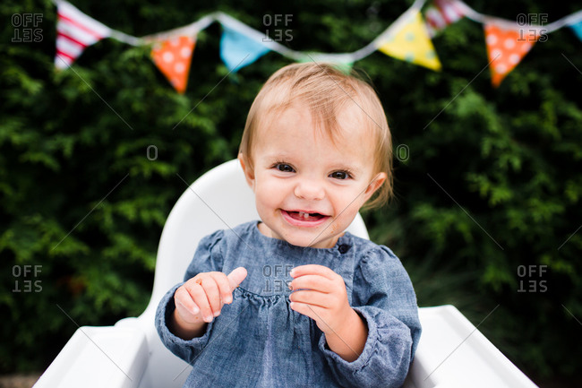 A baby smiles broadly during her birthday party