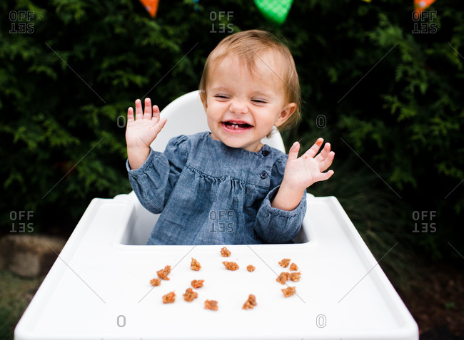 A baby laughs in her highchair