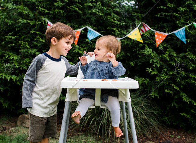 A boy makes his sister laugh during her birthday party