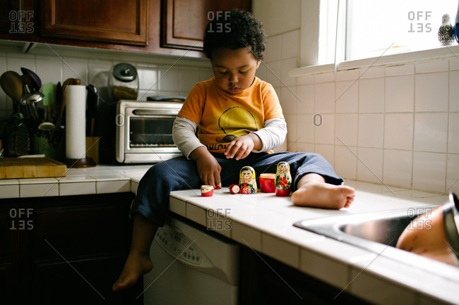 A boy plays on a kitchen counter