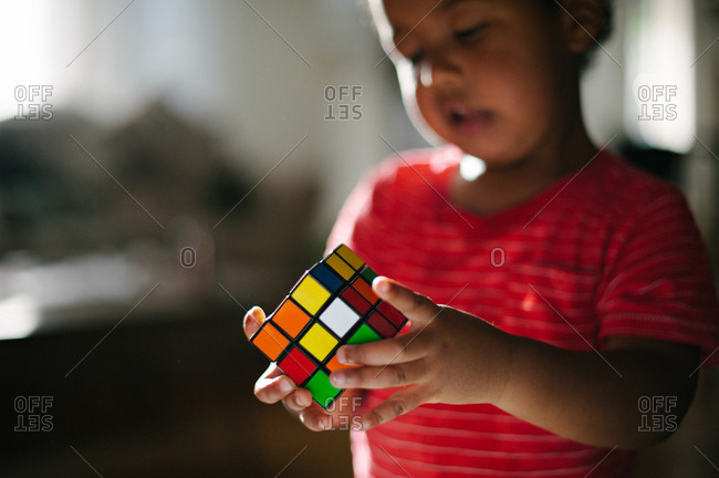 A boy looks at a Rubik's cube