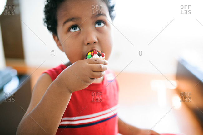 A boy eats a candy covered cupcake