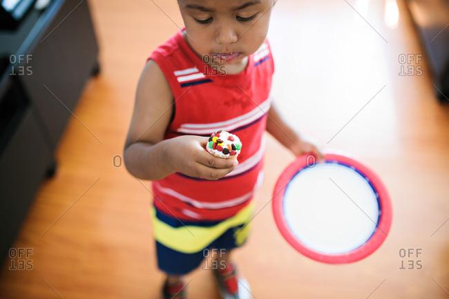 A boy holds a mini cupcake