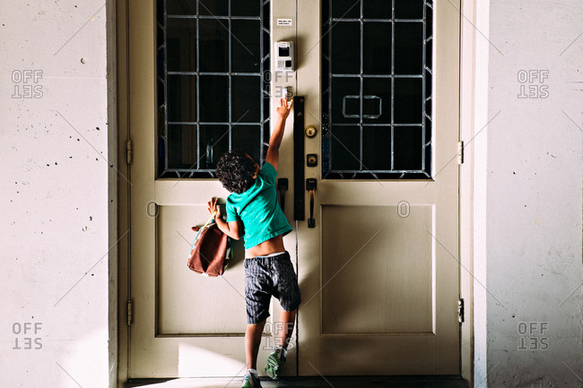 A boy reaches up to ring a doorbell