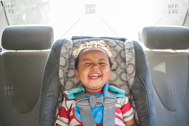 A baby boy smiles in his car seat