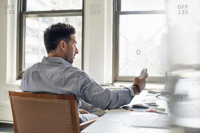A man at a desk checking his phone
