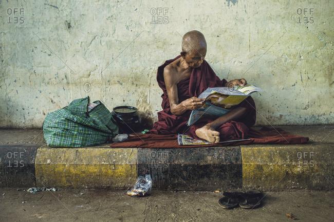 Yangon, Myanmar - September 18, 2012: Monk sitting legs crossed on floor reading newspaper