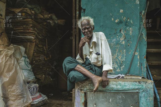 Yangon, Myanmar - September 2, 2012: Old man sitting with crossed legs on a ledge outside