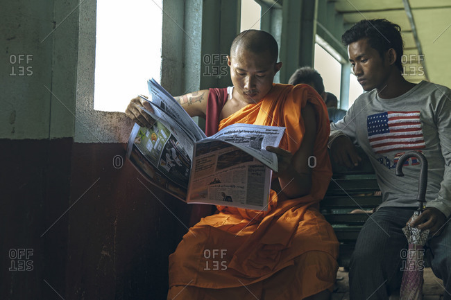 Yangon, Myanmar - September 2, 2012: Monk reading newspaper while a young man reads beside him