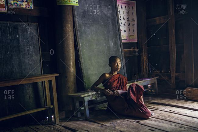 Mandalay, Myanmar - September 4, 2012: Young Buddhist monk sitting on floor of a pagoda