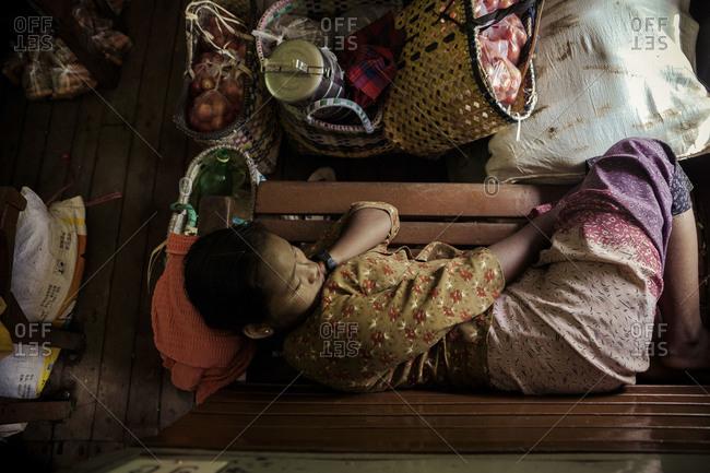 Mandalay, Burma - September 6, 2012: Woman sleeping on a train