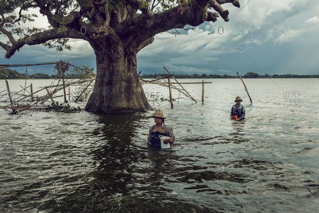 Myanmar, Southeast Asia - September 8, 2012: Women fishing under the U Bein bridge near Amarapura, Burma