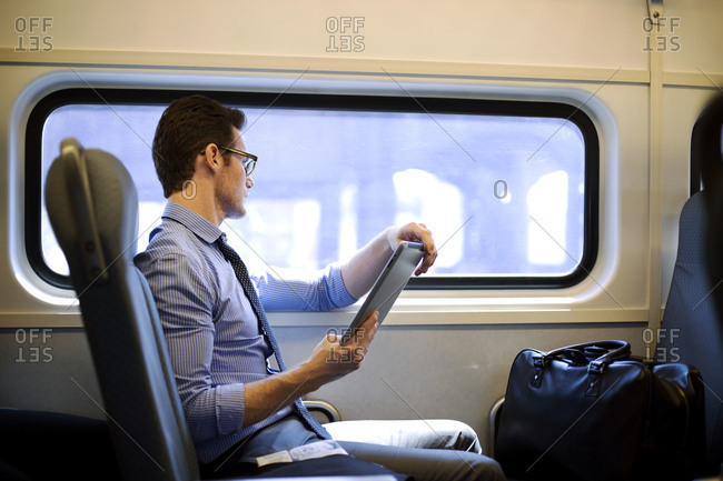 A man looking out commuter train window