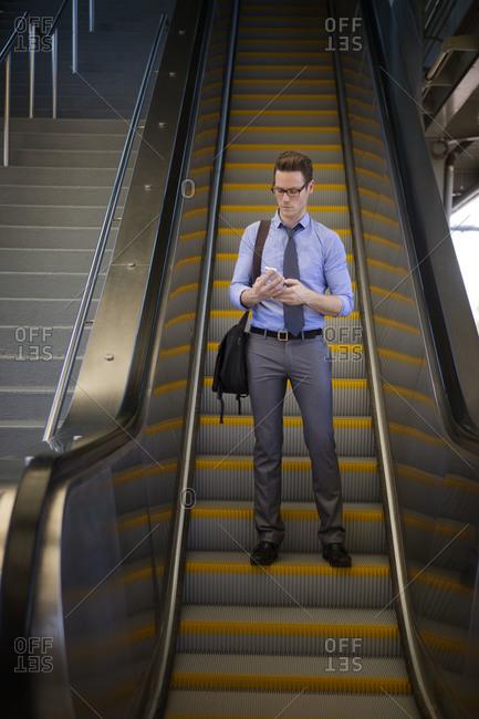 Man looking at phone on escalator
