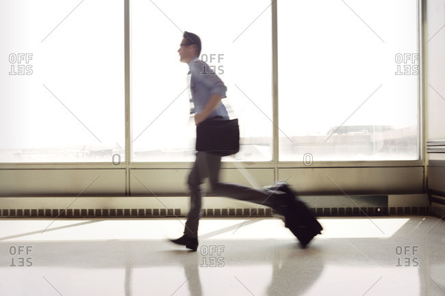 Man running down airport terminal
