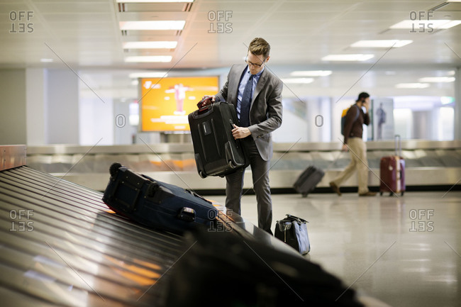 Man picking up luggage in airport