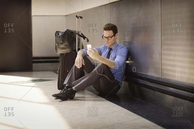 Man charging phone in airport