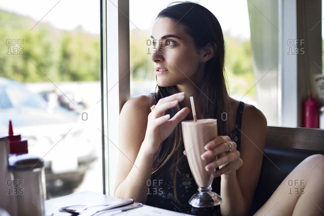 Woman in diner drinking milkshake