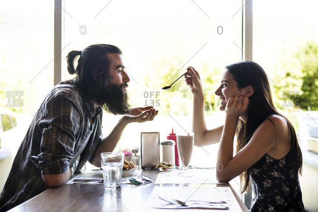 Woman and man sharing milkshake
