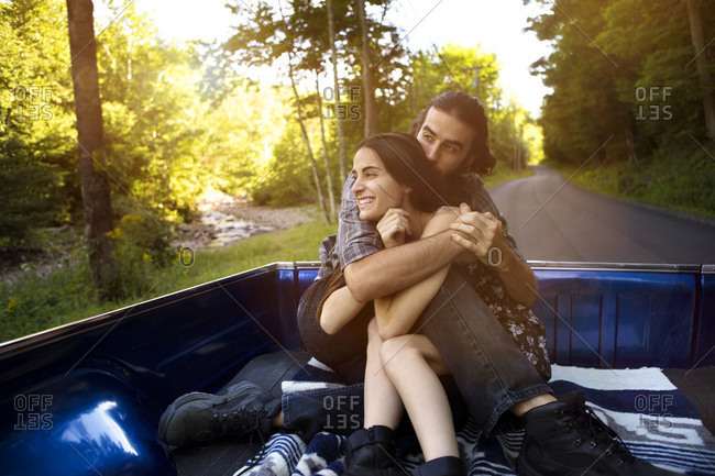 Couple cuddling in truck bed
