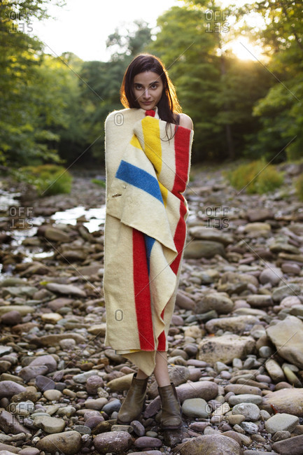 Woman in blanket by river