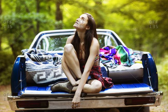 Woman in back of truck gazing
