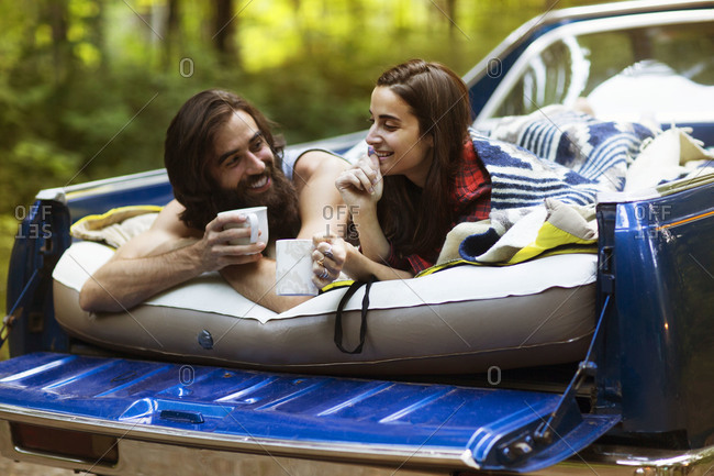 Couple drinking coffee in truck bed