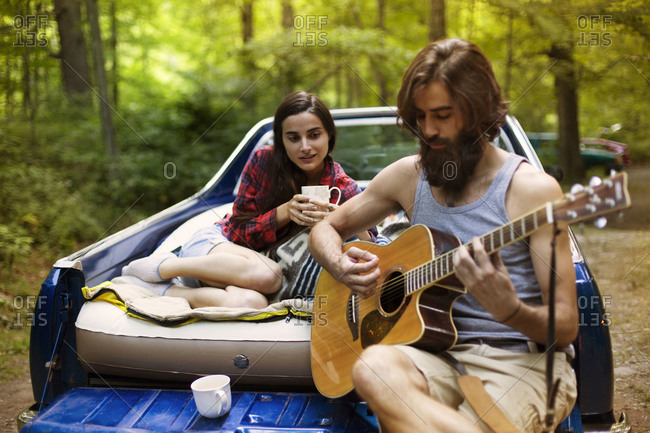 Man playing guitar for woman in back of truck