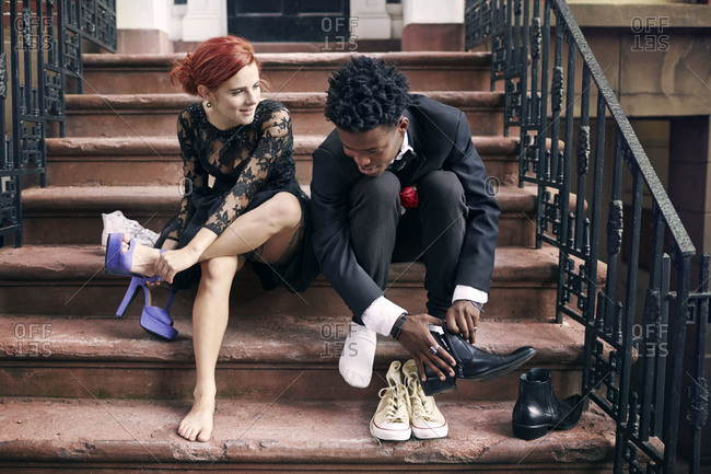 A couple on stoop changing shoes