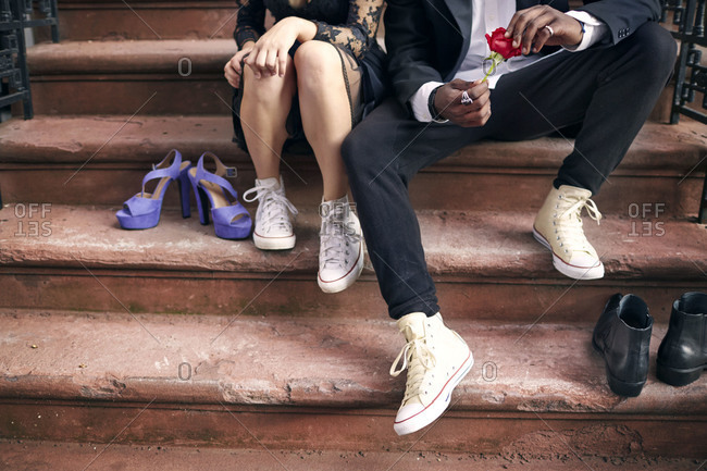 A couple on stoop in sneakers