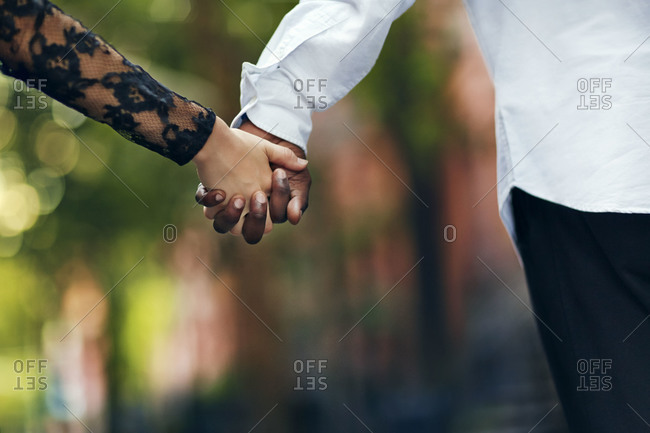 Couple in dress clothes holding hands